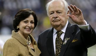 FILE - In this Nov. 10, 2013, file photo, New Orleans Saints owner Tom Benson, right, waves with his wife Gayle Benson before an NFL football game against the Dallas Cowboys in New Orleans. Benson and trustees for his estranged heirs have ironed out legal and structural sticking points of a settlement that has been in the works since last June, avoiding a federal trial that was scheduled to begin on Monday, Feb. 6, 2017. (AP Photo/Bill Haber, File)