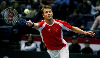 Switzerland's Marco Chiudinelli reaches to hit a shot from United States' Jack Sock during a Davis Cup tennis match Friday, Feb. 3, 2017, in Birmingham, Ala. (AP Photo/Butch Dill)