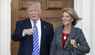 Then-President-elect Donald Trump, left, and Betsy DeVos, right, pose for photographs at Trump National Golf Club Bedminster's clubhouse in Bedminster, N.J., in this Nov. 19, 2016, file photo. (AP Photo/Carolyn Kaster, File)