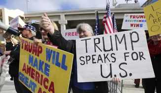 A woman gives a thumbs up as people in a passing car honk as demonstrators in favor of President Donald Trump's executive order banning travel to the U.S. from seven primarily Muslim nations stand across the street from the Tom Bradley International Terminal at Los Angeles International Airport Saturday, Feb. 4, 2017.  (AP Photo/Reed Saxon)