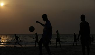 People plays soccer at sunset at the beach in Libreville, Gabon, Friday, Feb. 3, 2017. Libreville is holding the African Cup of Nations Final match on Sunday between Egypt and Cameroon, at the Stade de l'Amitie. (AP Photo/Sunday Alamba)