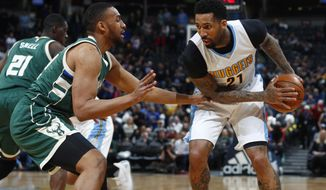 Denver Nuggets forward Wilson Chandler, right, looks to drive to the net as Milwaukee Bucks forward Jabari Parker defends in the first half of an NBA basketball game Friday, Feb. 3, 2017, in Denver. (AP Photo/David Zalubowski)