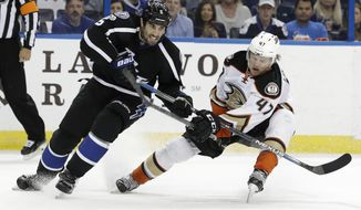 Tampa Bay Lightning defenseman Jason Garrison (5) keeps the puck away from Anaheim Ducks defenseman Hampus Lindholm (47), of Sweden, during the second period of an NHL hockey game Saturday, Feb. 4, 2017, in Tampa, Fla. (AP Photo/Chris O'Meara)