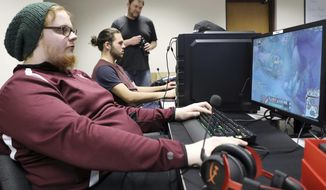 ADVANCE FOR SATURDAY, FEB. 4, 2017 - In this Thursday, Jan. 26, 2017 photo, Dean Stevens looks on as Derek Delzell, front, and Jared Amundson play video games while practicing with the eSports team at Morningside College in Sioux City, Iowa. (Jim Lee/Sioux City Journal via AP)