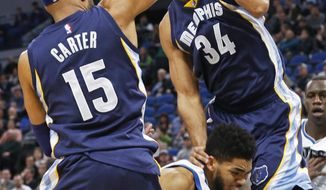 Minnesota Timberwolves' Karl-Anthony Towns, center, gets squeezed between Memphis Grizzlies' Vince Carter, left, and Brandan Wright who fouls him during the first quarter of an NBA basketball game Saturday, Feb. 4, 2017, in Minneapolis. (AP Photo/Jim Mone)