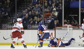 Carolina Hurricanes' Ron Hainsey (65) shoots the puck past New York Islanders goalie Jean-Francois Berube (30) during the second period of an NHL hockey game Saturday, Feb. 4, 2017, in New York. (AP Photo/Frank Franklin II)