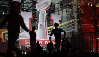 Fans play football outside of the NFL Experience ahead Super Bowl 51 Friday, Feb. 3, 2017, in Houston. The Atlanta Falcons will face the New England Patriots in the Super Bowl Sunday. (AP Photo/Eric Gay)