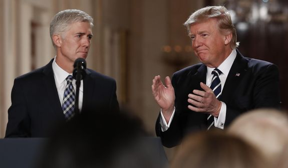 President Donald Trump applauds as he stands with Judge Neil Gorsuch in the East Room of the White House in Washington, after announcing Gorsuch as his nominee for the Supreme Court, int his Jan. 31, 2017, file photo. (AP Photo/Carolyn Kaster)