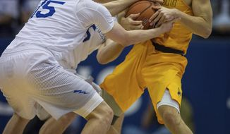 Air Force guards Jacob Van, left, and Zach Kocur force a jump ball against Wyoming guard Jeremy Lieberman during the first half of an NCAA college basketball game Saturday, Feb. 4, 2017,  in Colorado Springs, Colo. (Christian Murdock/The Gazette via AP)