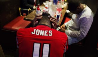 Atlanta Falcons fan CJ Scott hangs his head in his hands at Taco Mac restaurant in Atlanta after watching on television the New England Patriots beat Atlanta in the NFL Super Bowl 51 football game being played in Houston, Sunday, Feb. 5, 2017. The Patriots won 34-28 in overtime. (AP Photo/David Goldman)