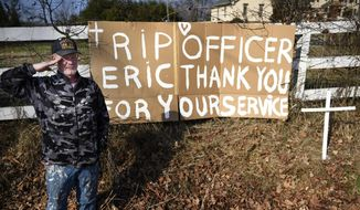 In this Thursday, Feb. 2, 2017 photo, Robert Brown salutes after hanging a sign along Neelys Bend Road in memory of Nashville Police Officer Eric Mumaw, who died while trying to save a woman in a water rescue in the Cumberland River Thursday morning, in Madison, Tenn. (Lacy Atkins/The Tennessean via AP)