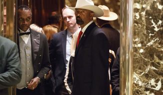 FILE - In this Nov. 28, 2016, file photo, Milwaukee County Sheriff David Clarke gets on an elevator after arriving at Trump Tower in New York. With a brash, unapologetic personality reminiscent of President Donald Trump, Clarke is positioning himself as an in-your-face conservative firebrand who has some Republicans swooning over his prospects for higher office. (AP Photo/Evan Vucci, File)