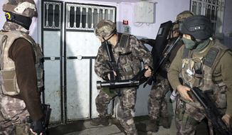 Turkish anti-terrorism police break a door during an operation to arrest people over alleged links to the Islamic State group, in Adiyaman, southeastern Turkey, early Sunday, Feb. 5, 2017. Turkey's state-run agency says anti-terrorism police have detained more than 400 people in simultaneous police operations that spanned several cities, including Istanbul and Gaziantep near the border with Syria, according to the report.   (Mahir Alan/Dha-Depo Photos via AP)