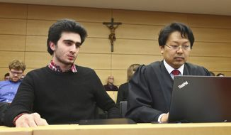 Anas Modamani, left, sits next to his lawyer Jun Chan-jo at the regional court in Wuerzburg, Germany, Monday Feb. 6, 2017.  The Syrian refugee pictured in a 2015 selfie with German Chancellor Angela Merkel is seeking an injunction that would oblige Facebook to identify and delete posts on its site which wrongly link him to crimes committed by migrants.  ( Karl-Josef Hildenbrand/dpa via AP)