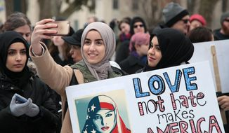 In a Sunday, Feb. 5, 2017 photo, two women take a selfie in Bronson Park during a rally in Kalamazoo against islamophobia and in support of the rights of Muslims, immigrants and refugees. Hundreds of people took part in new western Michigan protests of President Donald Trump's attempt to ban refugees and travelers from seven predominantly Muslim countries from entering the country.  (Jake Green/Kalamazoo Gazette-MLive Media Group via AP)