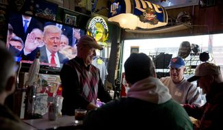 President Donald Trump is sworn in during a live broadcast of the inauguration as Denny Riebe, from right, Doug Dickman, Scott Reilly, and Bill Winter, play cards at the Sawmill Saloon in Prairie du Chien, Wis., Friday, Jan. 20, 2017. (AP Photo/David Goldman)