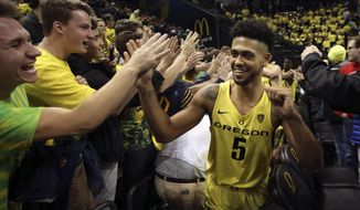 Oregon's Tyler Dorsey, right, celebrates with Duck fans after helping defeat Arizona in an NCAA college basketball game Saturday, Feb. 4, 2017, in Eugene, Ore. (AP Photo/Chris Pietsch)