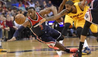 Washington Wizards guard John Wall, left, dives for a loose ball against Cleveland Cavaliers guard Kyrie Irving, right, during the first half of an NBA basketball game, Monday, Feb. 6, 2017, in Washington. (AP Photo/Nick Wass)