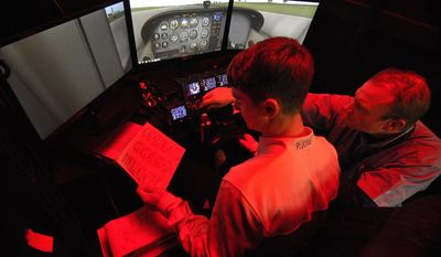 In a Jan. 30, 2017 photo,  North Coast Flight School, Edinboro University student Bryan Plucknett, 19, left, and chief flight instructor Jon Scott use a flight simulator in Millcreek Township, Pa. Plucknett, from Springfield Township, is enrolled in the school's Associate of Applied Science in Aeronautical Science program and hopes to become a commercial pilot when his training is complete. Former commercial pilot Scott, 42, said the red light used in the cockpit helps prevent excessive eye strain when flying. (Greg Wohlford/Erie Times-News via AP)