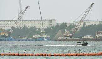 A boat goes by cranes being used for the preparation work to relocate a U.S. Marine base to Henoko  to dump large concrete blocks into sea along the shore in Nago, Okinawa Prefecture, southern Japan, Monday, Feb. 6, 2017. Japan's government has started offshore construction work on relocating a U.S. Marine base on Okinawa. Monday's step marks the beginning of the main construction to move Marine Corps Air Station Futenma to Henoko, a less populated area on the island. (Koji Harada/Kyodo News via AP)