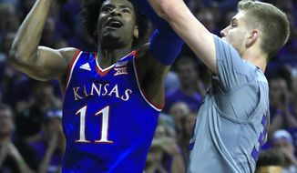 Kansas guard Josh Jackson (11) shoots while covered by Kansas State forward Dean Wade (32) during the first half of an NCAA college basketball game in Manhattan, Kan., Monday, Feb. 6, 2017. (AP Photo/Orlin Wagner)