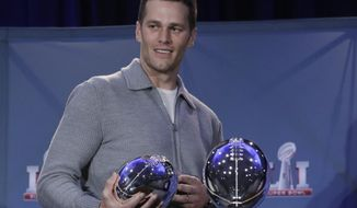 New England Patriots quarterback Tom Brady walks off with his MVP trophy during a news conference after the NFL Super Bowl 51 football game Monday, Feb. 6, 2017, in Houston. (AP Photo/Morry Gash)