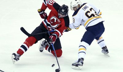 New Jersey Devils center Sergey Kalinin (51), of Russia, falls as he tries to control the puck around Buffalo Sabres forward Tyler Ennis (63) during the first period of an NHL hockey game, Monday, Feb. 6, 2017, in Newark, N.J. (AP Photo/Mel Evans)