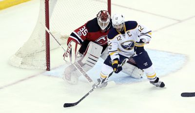 Buffalo Sabres right wing Brian Gionta (12) goes for the puck in front of New Jersey Devils goalie Cory Schneider (35) during the first period of an NHL hockey game, Monday, Feb. 6, 2017, in Newark, N.J. (AP Photo/Mel Evans)