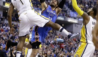 Oklahoma City Thunder center Steven Adams (12) is fouled as he shoots between Indiana Pacers center Kevin Seraphin (1) and forward Paul George (13) during the first half of an NBA basketball game in Indianapolis, Monday, Feb. 6, 2017. (AP Photo/Michael Conroy)