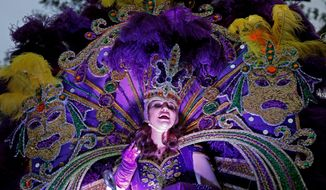 FILE - In this Feb. 6, 2016, file photo, a maid from the royal court of Endymion throws beads as the Krewe of Endymion Mardi Gras parade rolls through New Orleans. New Orleans is entering the height of its annual pre-Lenten Carnival season, culminating on Mardi Gras, or Fat Tuesday, which falls on Feb. 28 this year. Travelers to the city face an abundance of choices on how, when and where to take it all in. (AP Photo/Gerald Herbert, File)