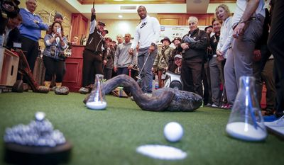 Arizona Cardinals wide receiver Larry Fitzgerald, center, putts a hole-in-one on an indoor putting green during the Chevron's 7th annual $100,000 Shoot-Out in the Champions vs Champions to kick off the AT&T National Pro-Am golf tournament on Tuesday, Feb. 7, 2017, in Pebble Beach, Calif. Since 2013, Chevron has provided over $500,000 to local nonprofits and education organizations through this event. (Tony Avelar/AP Images for Chevron)