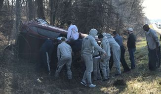 Georgetown basketball players assist an overturned car involved in a traffic accident on I-95 North outside of Baltimore on Monday afternoon. (Courtesy of Georgetown University Athletics).