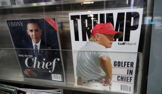 Appearing on a New York newsstand are Ebony magazine, left, featuring former President Barack Obama, and President Donald Trump on the cover of Golf Digest, Jan. 26, 2017. (AP Photo/Mark Lennihan)