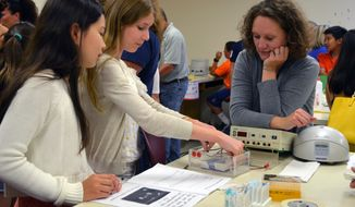 In this photo provided by Cold Spring Harbor Laboratory, DNA Learning Center Assistant Director Amanda McBrien looks on as World of Enzymes camp participants set up apparatus for gel electrophoresis in Cold Spring Harbor, N.Y. (Chun-hua Yang/Cold Spring Harbor Laboratory via AP)