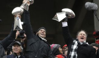 New England Patriots quarterback Tom Brady holds up Super Bowl trophies along with head coach Bill Belichick, right, and team owner Robert Kraft, left, during a rally Tuesday, Feb. 7, 2017, in Boston, to celebrate Sunday's 34-28 win over the Atlanta Falcons in the NFL Super Bowl 51 football game in Houston. (AP Photo/Elise Amendola)