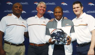 Denver Broncos head coach Vance Joseph, third from left, joins defensive coordinator Joe, Woods, far left, offensive coordinator Mike McCoy, second from left, and special teams coach Brock Olivo for a photograph following a news conference to showcase the new hires, Tuesday, Feb. 7, 2017, at the team's headquarters in Englewood, Colo. The new coaches said that the goal is to build on the strengths of the team's defense while enhancing the Broncos' anemic offense. (AP Photo/David Zalubowski)