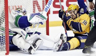 Nashville Predators left wing Viktor Arvidsson (38), of Sweden, laughs after he and Vancouver Canucks goalie Jacob Markstrom (25), also of Sweden, both ended up on the ice during the second period of an NHL hockey game Tuesday, Feb. 7, 2017, in Nashville, Tenn. (AP Photo/Mark Humphrey)