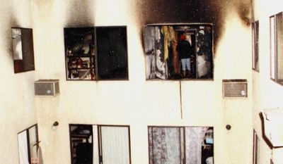 In this May 1993 photo provided by the Los Angeles Police Department, on display at a news conference, investigators attend the scene of a deadly fire that struck an apartment building in the Westlake district of Los Angeles, taking the lives of 12 people including the deaths of late-term fetuses. Police Chief Charlie Beck said Monday, Feb. 6, 2017, that two men were arrested Feb. 3 and a woman was already in custody in connection with the fire. One suspect was still being sought. (Los Angeles Police Department via AP)