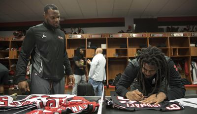 Atlanta Falcons defensive back Kemal Ishmael, right, autographs a jersey for middle linebacker LaRoy Reynolds in the locker room at the team's practice facility, Tuesday, Feb. 7, 2017, in Flowery Branch, Ga. (Branden Camp/Atlanta Journal-Constitution via AP)
