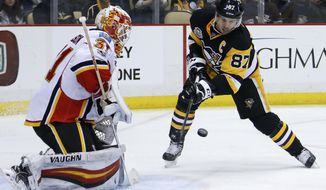 Pittsburgh Penguins' Sidney Crosby (87) can't get a shot past Calgary Flames goalie Chad Johnson during the second period of an NHL hockey game in Pittsburgh, Tuesday, Feb. 7, 2017. (AP Photo/Gene J. Puskar)