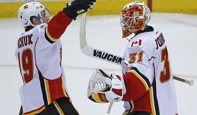 Calgary Flames' Matthew Tkachuk (19) and goalie Chad Johnson (31) celebrate the Flames' 3-2 win over the Pittsburgh Penguins, following the shootout during an NHL hockey game in Pittsburgh, Tuesday, Feb. 7, 2017.. (AP Photo/Gene J. Puskar)
