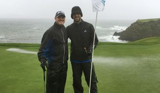 PGA Tour veteran Jerry Kelly, left, and Green Bay quarterback Aaron Rodgers pose on the 8th green at Pebble Beach, Calif., on Tuesday, Feb. 7, 2017, while playing in 40 mph wind and rain. Only at Pebble Beach are players willing to go out in such miserable conditions.  (AP Photo/Doug Ferguson)