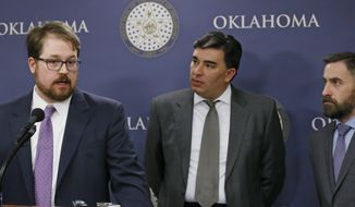 Attorney Blake Lawrence, left, answers a question about a lawsuit against Oklahoma Attorney General Scott Pruitt over public access to official emails, in Oklahoma City, Tuesday, Feb. 7, 2017. Looking on are Brady Henderson, center, and Ryan Kiesel, both of the American Civil Liberties Union of Oklahoma. A lawsuit filed against Pruitt, President Donald Trump's pick to head the Environmental Protection Agency, accuses him of violating the state open records law by not providing access to emails and other official documents sought for up to two years. (AP Photo/Sue Ogrocki)