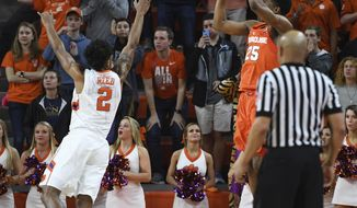 Syracuse guard Tyus Battle (25) shoots a 3-pointer over Clemson guard Marcquise Reed (2) as time expires to give Syracuse an 82-81 in an NCAA college basketball game in Clemson, S.C., Tuesday,  Feb. 7, 2017. (Bart Boatwright/The Greenville News via AP)