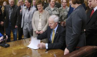 Arkansas Gov. Asa Hutchinson signs a bill in his Capitol conference room in Little Rock on Tuesday, Feb. 7, 2017, to cut income taxes on military retirement benefits as Sen. Jane English, center, looks on. The tax cut is intended to help promote economic development by attracting retirees to the state. Arkansas will raise taxes on unemployment benefits, soda, candy and digital downloads to pay for it. (AP Photo/Kelly P. Kissel)