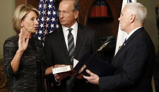 Vice President Mike Pence swears in Education Secretary Betsy DeVos in the Eisenhower Executive Office Building in the White House complex in Washington, Tuesday, Feb. 7, 2016, as DeVos' husband Dick DeVos watches. (AP Photo/Pablo Martinez Monsivais)