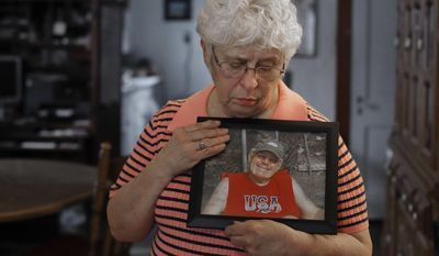 In this Thursday, Jan. 26, 2017, photo, Kay Taynor holds a photo of her late husband, Gary, in Toledo, Ohio. Dozens of patients from a now-closed memory loss clinic in Ohio say its director told them they had Alzheimer's disease when they really didn't. More than 50 people have sued, saying they thought for months they had the mind-robbing disease. Taynor was diagnosed with Alzheimer's on her second visit to clinic director Sherry-Ann Jenkins and then referred five or six friends and family members to her office, including her husband of 48 years. All were told they had the disease, she said, but her husband, Gary, took it hardest. (AP Photo/Paul Sancya)