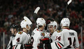 Chicago Blackhawks' Jonathan Toews pats teammate Nick Schmaltz on the helmet after Schmaltz scored the second goal in the second period of an NHL hockey game against the Minnesota Wild, Wednesday, Feb. 8, 2017, in St. Paul, Minn. (AP Photo/Stacy Bengs)