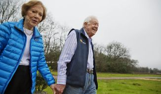 Former President Jimmy Carter, right, and his wife Rosalynn arrive for a ribbon cutting ceremony for a solar panel project on farmland he owns in their hometown of Plains, Ga., Wednesday, Feb. 8, 2017. Carter leased the land to Atlanta-based SolAmerica Energy, which owns, operates, and sells power generated from solar cells. The company estimates the project will provide more than half of the power needed in this town of 755 people. (AP Photo/David Goldman)