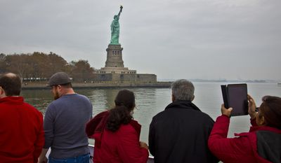 FILE - In this Nov. 5, 2015, file photo, visitors view the Statue of Liberty during a ferry ride to Liberty Island in New York. The travel industry is debating whether President Donald Trump's ban on travel from seven countries will have a larger impact on tourism in the U.S. Some experts say the controversy will have no effect while others worry that it sends an unwelcoming message to travelers around the world. An op-ed piece in the Toronto Star on Jan. 30, 2017,  encouraged Canadians to boycott the U.S. for now, saying that the Statue of Liberty will still be there in a few years. (AP Photo/Bebeto Matthews, File)